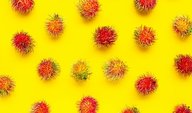 Bovenaanzicht van rambutan fruit op gele achtergrond. kopieer ruimte