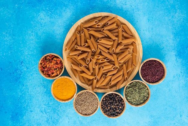 Bovenaanzicht van rauw bruin verleden op een houten bord en verschillende soorten kruiden over blauw oppervlak.