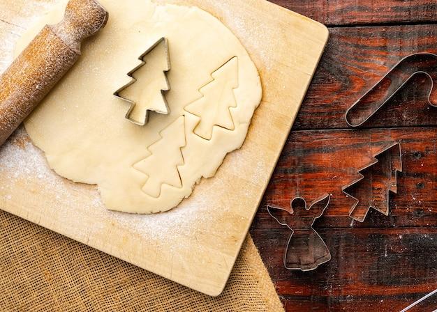 Bovenaanzicht van rauw deeg en kerstkoekjessnijders op rustieke keukentafel