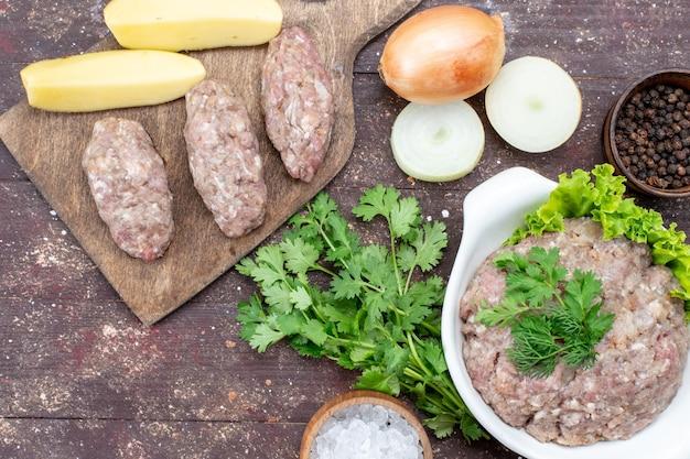 Bovenaanzicht van rauw gehakt met groenen binnen plaat met uien rauwe aardappelen zout op bruin sluiten