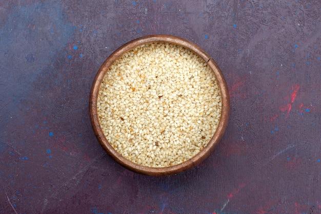 Bovenaanzicht van rauw product in ronde bruine pot op donkere ondergrond