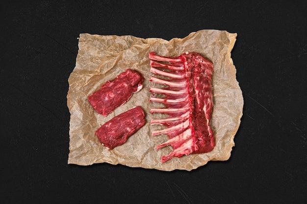 Bovenaanzicht van rauw vers lamsrack en biefstuk in inpakpapier