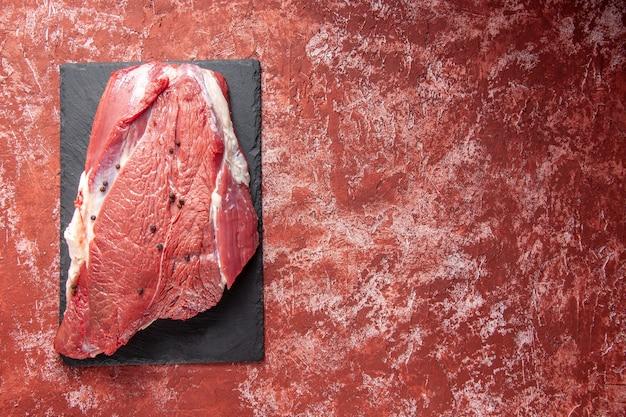Bovenaanzicht van rauw vers rood vlees op zwart bord aan de rechterkant op oliepastelrode achtergrond met vrije ruimte