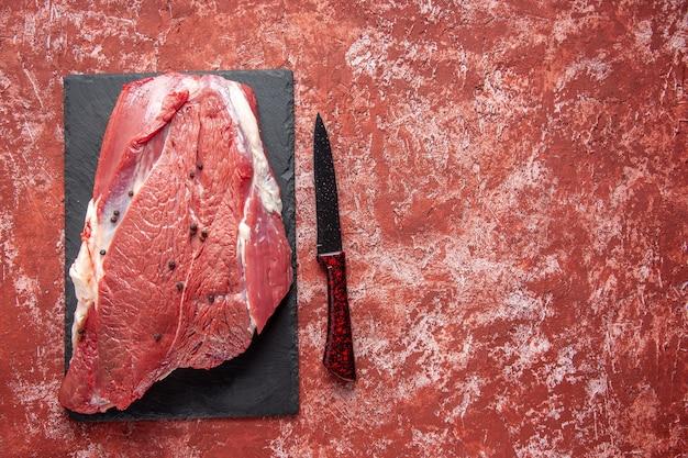 Bovenaanzicht van rauw vers rood vlees op zwart bord en mes aan de rechterkant op oliepastelrode achtergrond met vrije ruimte