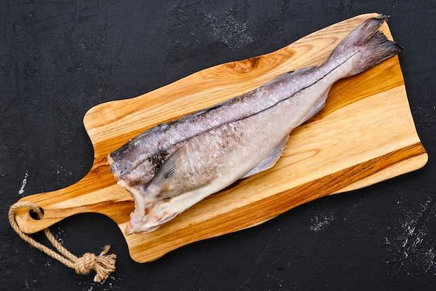 Bovenaanzicht van rauw vers schelvis karkas op houten snijplank