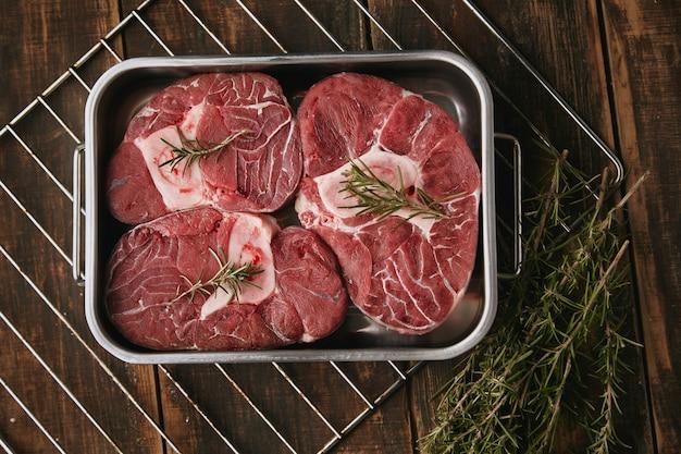 Bovenaanzicht van rauw vlees in stalen pan klaar om te koken in de oven. kruiden rond: peper, knoflook, rozemarijn, uien. zout. saus pot. warme tinten.