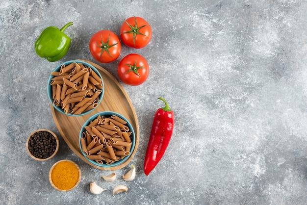 Bovenaanzicht van rauwe bruine pasta met groente en kruiden op grijze ondergrond.
