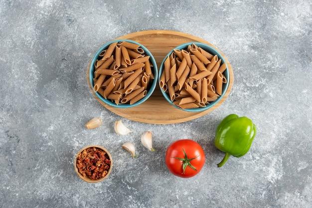 Bovenaanzicht van rauwe dieetpasta in twee kom over houten bord met groenten.