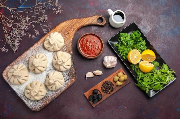 Bovenaanzicht van rauwe dumplings deeg met tomatensaus en citroen op zwart