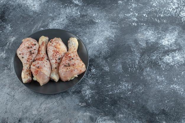 Bovenaanzicht van rauwe gemarineerde kippenpoten op zwarte plaat.