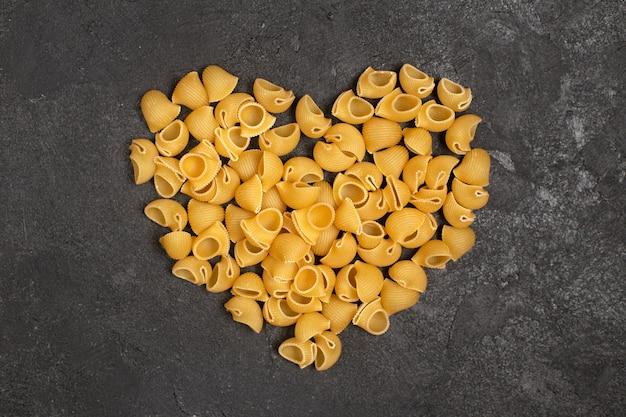 Bovenaanzicht van rauwe italiaanse pasta die hartvorm op het donkere oppervlak vormt