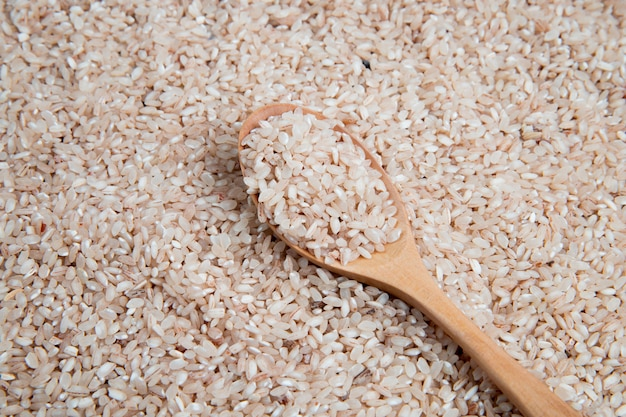 Bovenaanzicht van rauwe ongekookte witte rijst in een houten lepel op het oppervlak volledig bedekt met rauwe rijst