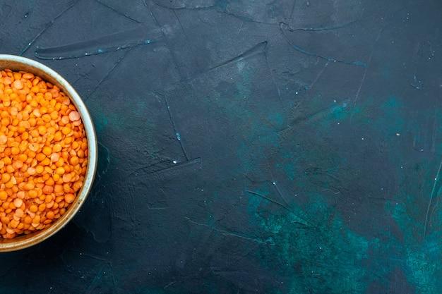 Bovenaanzicht van rauwe oranje linze in ronde pot op het donkerblauwe oppervlak