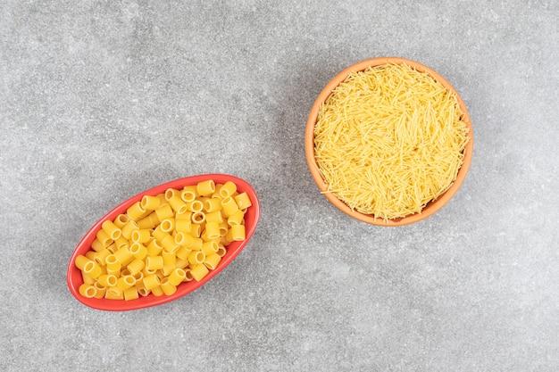 Bovenaanzicht van rauwe pasta en vermicelli op grijze tafel.