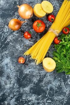 Bovenaanzicht van rauwe pasta met aardappel, peterselie en tomaten op lichtgrijs oppervlak
