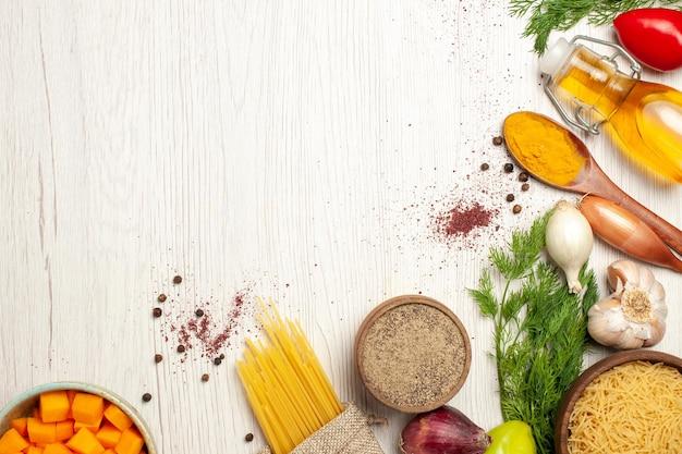Bovenaanzicht van rauwe pasta met greens en groenten op witte tafel