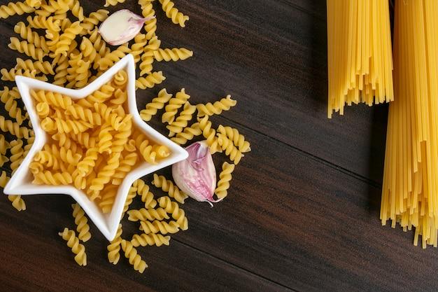 Bovenaanzicht van rauwe pasta met knoflook en spaghetti op een houten oppervlak