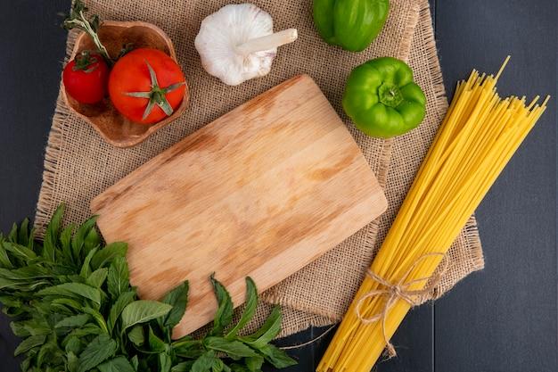 Bovenaanzicht van rauwe pasta met snijplank tomaten knoflook munt en paprika op een beige servet