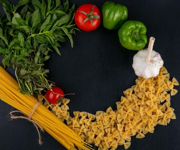 Bovenaanzicht van rauwe pasta met spaghetti tomaten knoflook en paprika met munt op een zwarte ondergrond