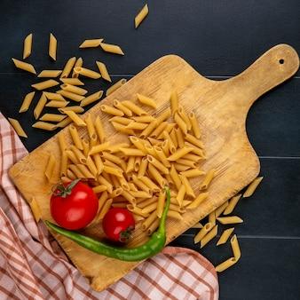 Bovenaanzicht van rauwe pasta met tomaten en chili peper op een snijplank op een zwarte ondergrond