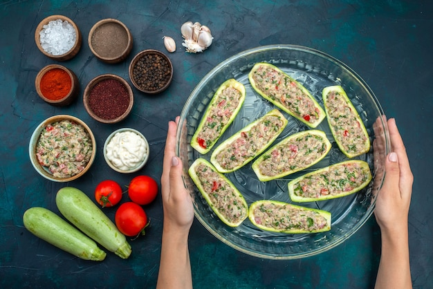 Bovenaanzicht van rauwe pompoenen met pittig gehakt samen met groenten en kruiden op het donkerblauwe oppervlak
