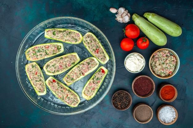 Bovenaanzicht van rauwe pompoenen met pittig gehakt samen met groenten op het donkerblauwe oppervlak