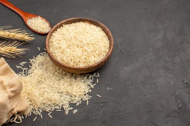 Bovenaanzicht van rauwe rijst in bruine plaat op het grijze oppervlak