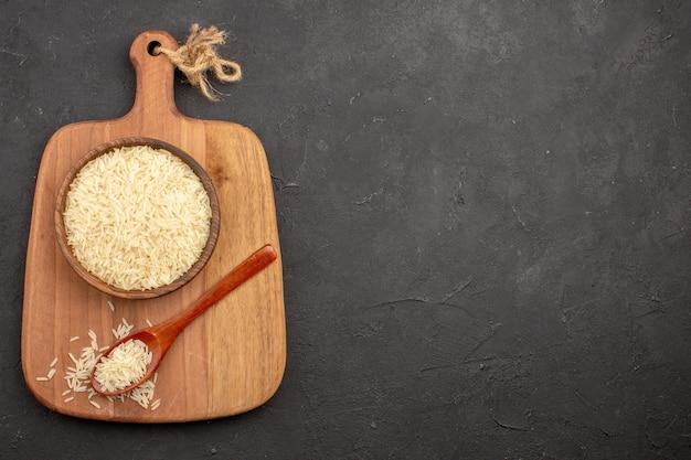 Bovenaanzicht van rauwe rijst in houten bruine plaat op het grijze oppervlak