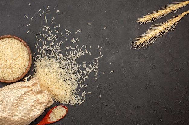Bovenaanzicht van rauwe rijst in zak en plaat op grijze ondergrond