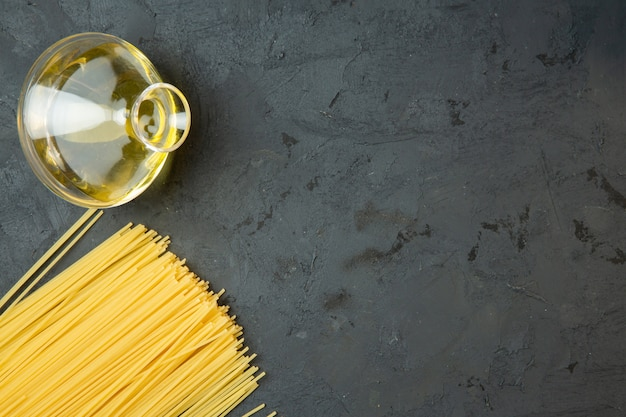 Bovenaanzicht van rauwe spaghetti en een fles olijfolie met kopie ruimte op zwart