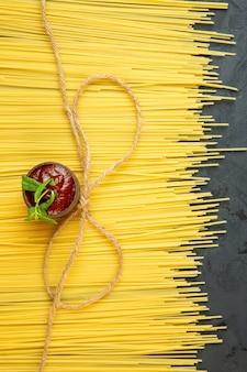 Bovenaanzicht van rauwe spaghetti en ketchup in schotel op zwart
