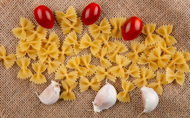 Bovenaanzicht van rauwe spaghetti met kerstomaatjes en knoflook op een beige servet