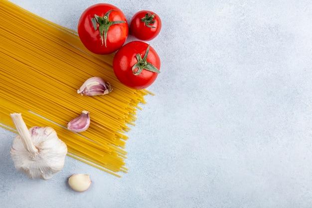 Bovenaanzicht van rauwe spaghetti met knoflook en tomaten op een grijze ondergrond