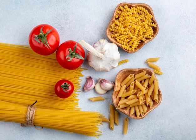 Bovenaanzicht van rauwe spaghetti met rauwe pasta in kommen met knoflook en tomaten op een grijze ondergrond