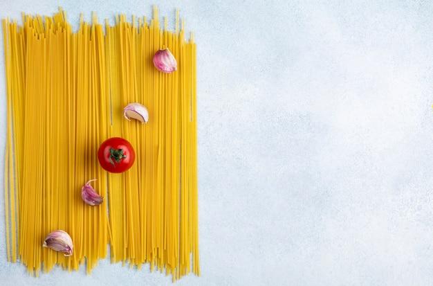 Bovenaanzicht van rauwe spaghetti met tomaat en knoflook op een grijze ondergrond