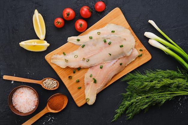 Bovenaanzicht van rauwe verse schelvisfilet op houten snijplank met specerijen en kruiden