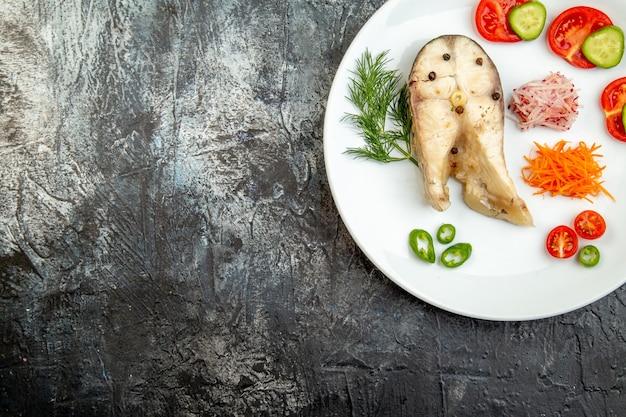 Bovenaanzicht van rauwe vissen en peper vers voedsel op witte plaat aan de linkerkant op ijsoppervlak met vrije ruimte
