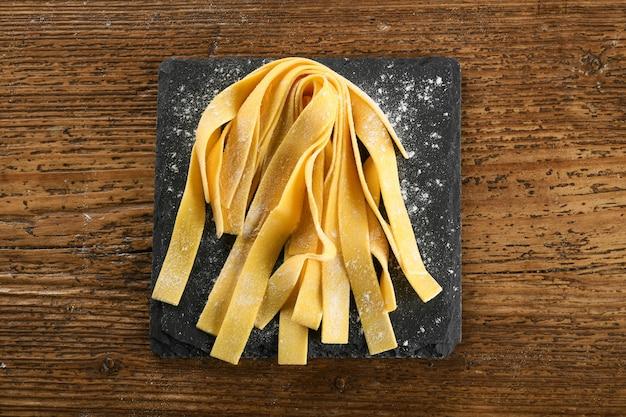 Bovenaanzicht van rauwe zelfgemaakte traditionele italiaanse pappardelle pasta op zwarte leisteen bord besprenkeld met bloem op houten tafel