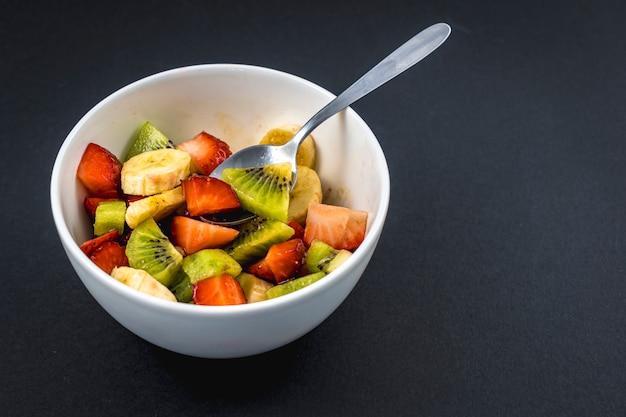 Bovenaanzicht van recept voor een fruitsalade met kiwi's, aardbeien, bananen op zwart
