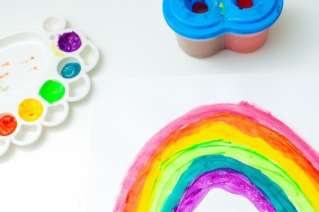 Bovenaanzicht van regenboog geschilderd met een penseel door aquarellen op een vel wit papier. blijf thuis en coronavirus pandemie concept concept. regenboog tekening.
