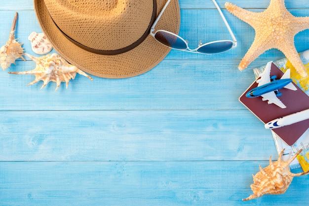 Bovenaanzicht van reisaccessoires op lichtblauwe houten plankenvloer voor zomervakantie