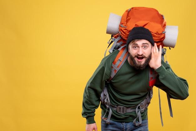 Bovenaanzicht van reisconcept met jonge kerel die met packpack luistert naar de laatste roddelen