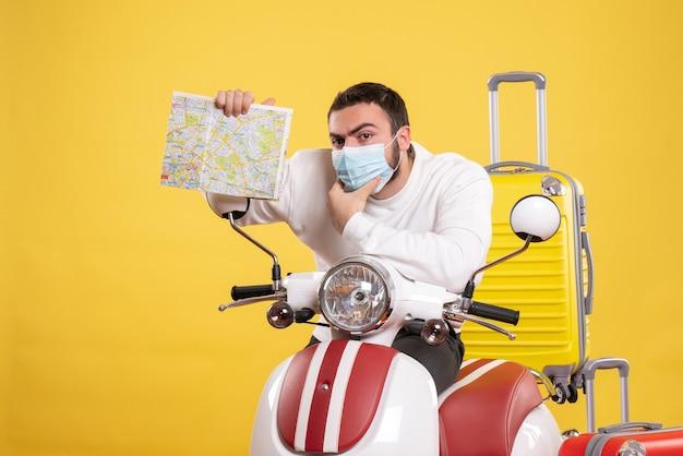 Bovenaanzicht van reisconcept met jonge kerel met medisch masker die in de buurt van motorfiets staat