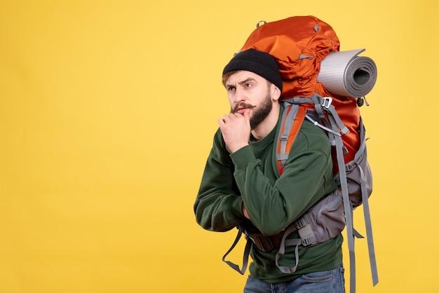 Bovenaanzicht van reisconcept met jonge kerel met packpack in diepe gedachten