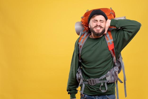Bovenaanzicht van reisconcept met nerveuze emotionele jonge kerel met packpack die zijn oor sluit