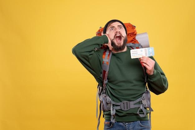 Bovenaanzicht van reisconcept met nerveuze emotionele jonge kerel met packpack en iemand bellen