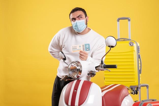 Bovenaanzicht van reisconcept met nieuwsgierige jonge kerel met medisch masker die in de buurt van motorfiets staat