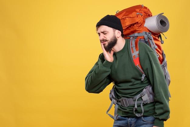 Bovenaanzicht van reisconcept met onrustige jonge kerel met packpack die lijdt aan kiespijn