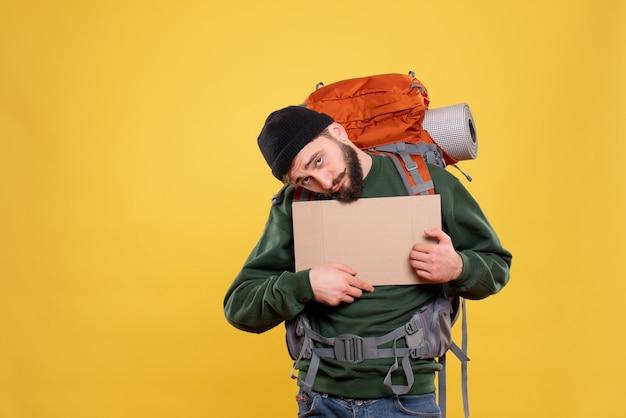 Bovenaanzicht van reisconcept met vermoeide jonge kerel met packpack met vrije ruimte om te schrijven