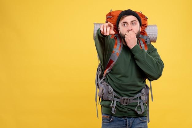 Bovenaanzicht van reisconcept met verrast jonge kerel met packpack naar voren gericht
